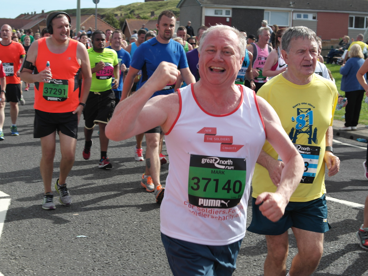 """North East Committee member Mark Allison celebrating as he runs the last mile of the Great North Run in aid of The Soldiers' Charity"""""""