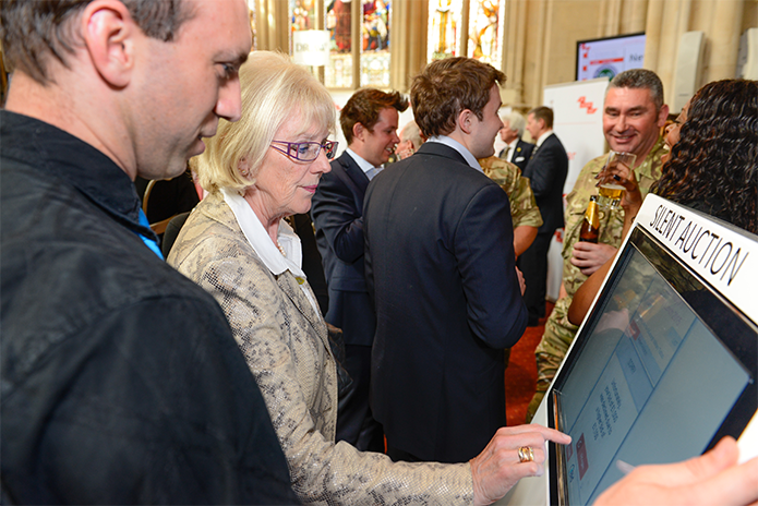 An attendee at the Lord Mayor's Big Curry Lunch places a bid on the silent auction in 2015